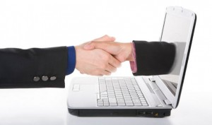 Handshake concept between a businessman and a person from laptop's screen.